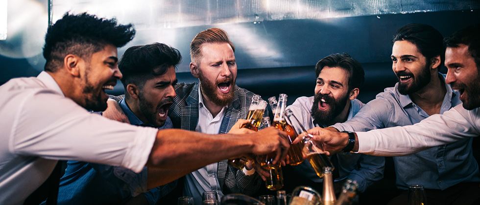 A group of young men bring their beer bottles together in a toast