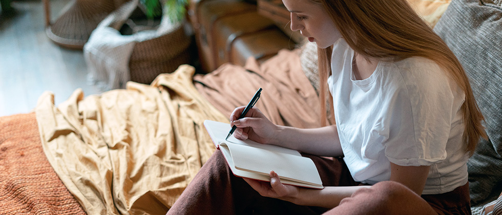 A young woman sits on her bed writing in a notebook