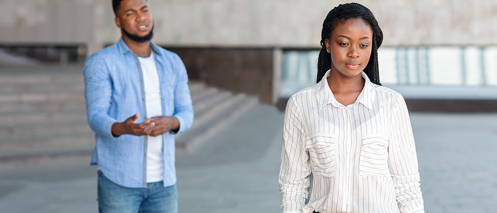 A young woman walks away from her male partner, who beseeches her to stay