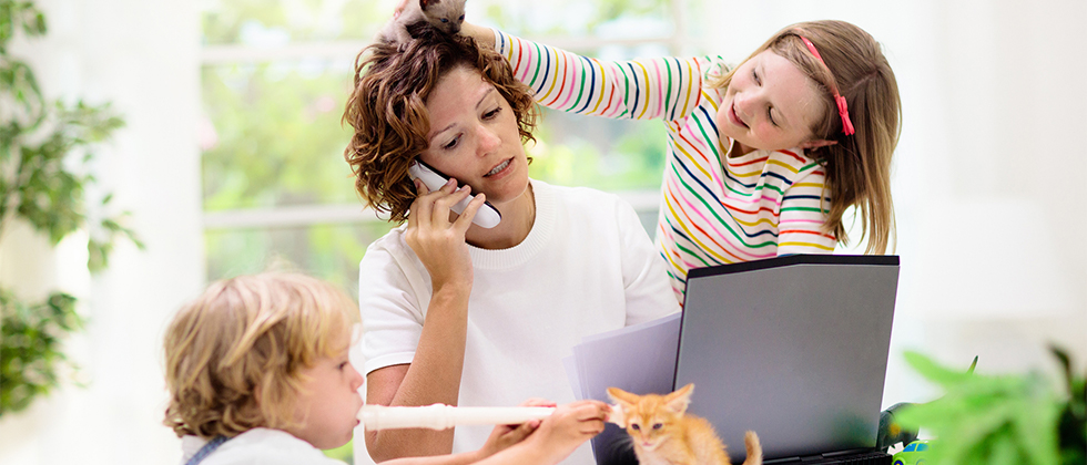 A woman trying to work at a computer, but two kids are distracting her