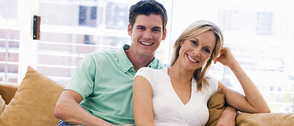 A young man and slightly older woman look to camera from their sofa