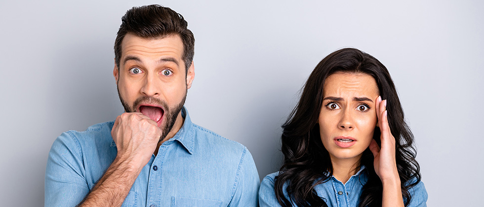 A similarly dressed couple look to camera with an expression of surprise