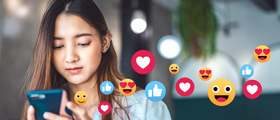 A young woman looks at her phone while animated social media icons float across the picture