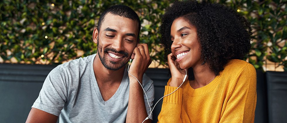 A young couple sit in a café, sharing a set of earphones listening to music