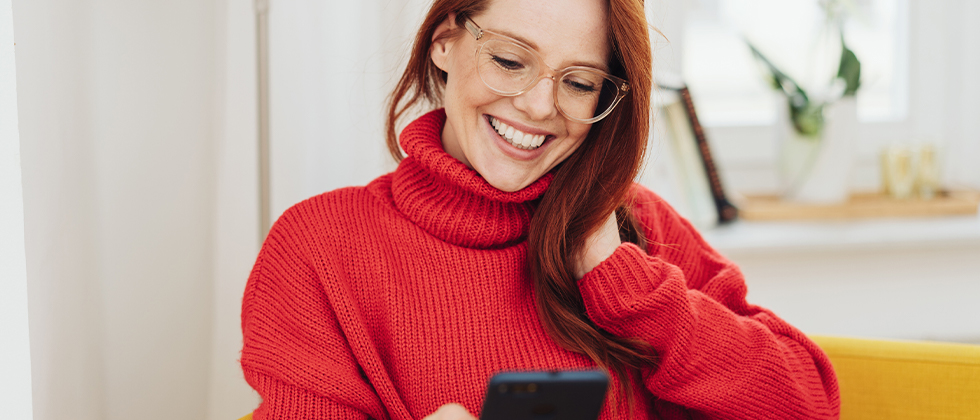 A woman smilling and looking at her phone