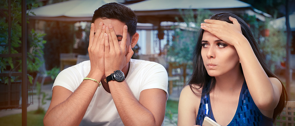 A woman stares in exasperation at her date, who holds his head in his hands