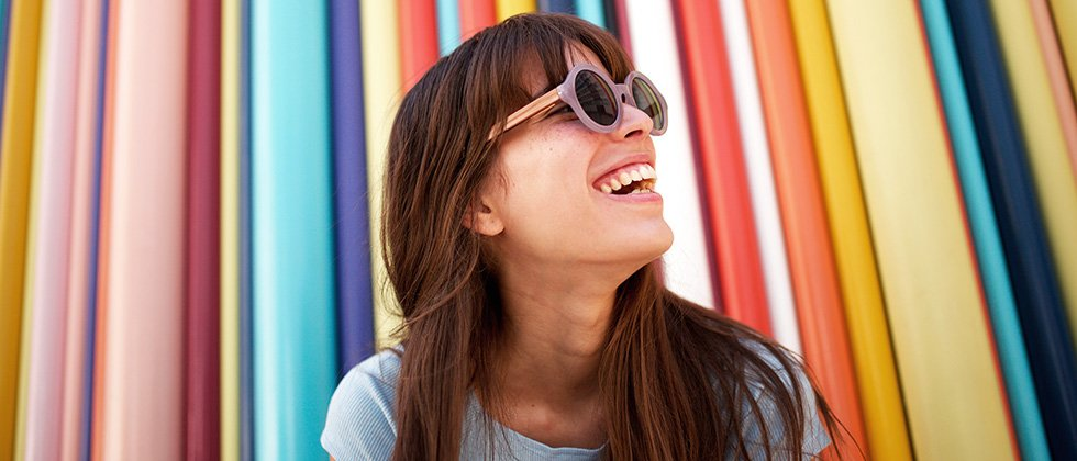 A woman in sunglasses in front of a colourful, striped background