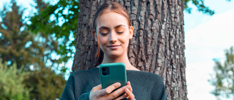 A young woman stands in front of a tree, sending a message on her phone