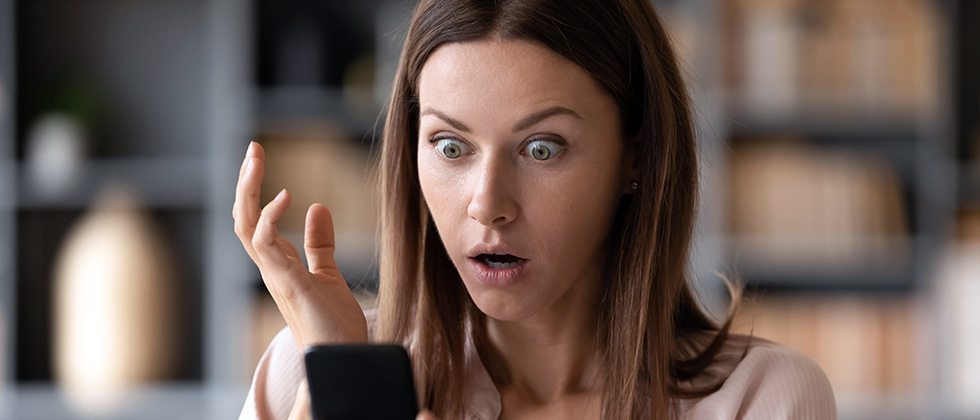 A young woman looks at her phone with an expression of shock on her face