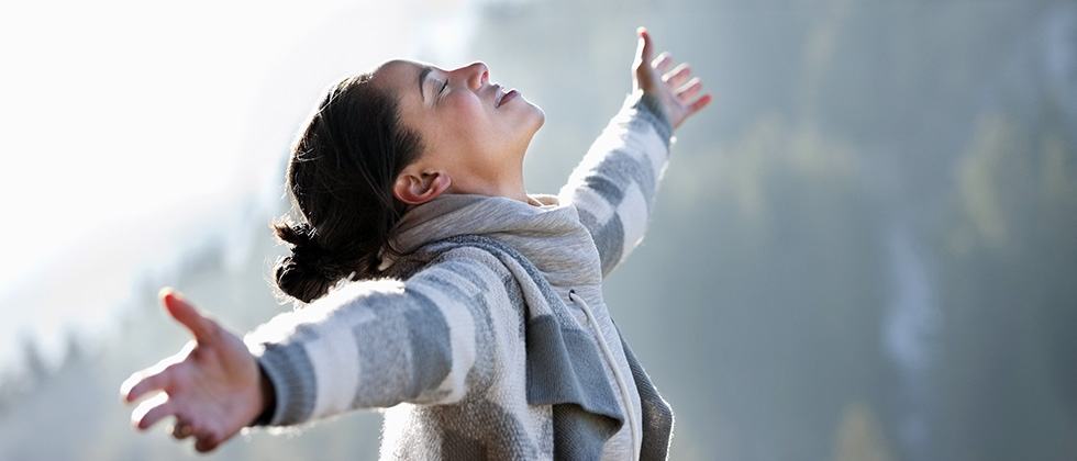 A woman stands with open arms, her face raised to the sky