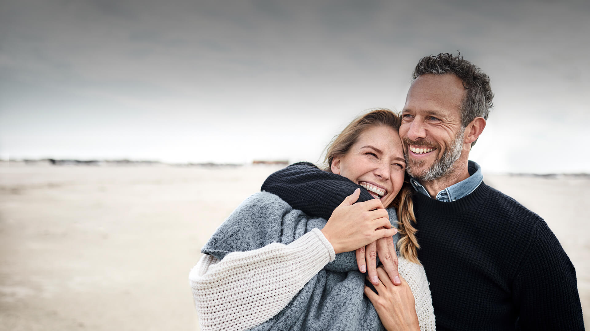 Catholic dating in Australia symbolized by a man who hold a woman in his arms at the beach