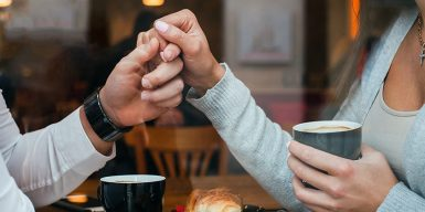 A couple hold hands over a table in a cafe