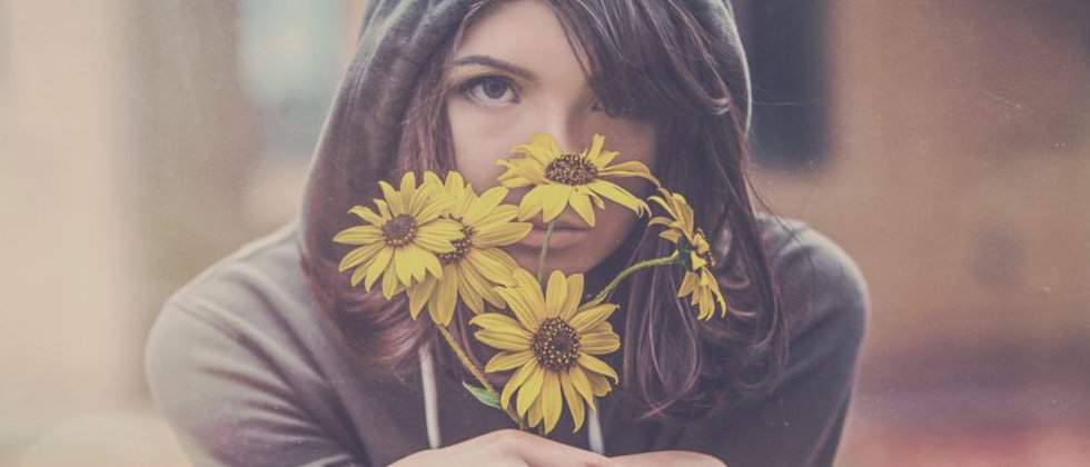 Sad woman holding a bouquet of wilting flowers