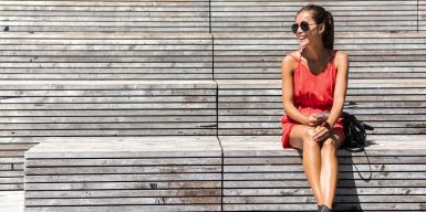 Pretty woman smiling and sitting alone on a park bench