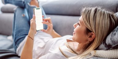 Woman laying on her couch casually while holding her phone